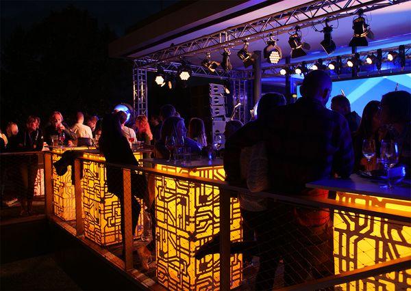 G+B Afterwork Party gelb beleuchtete ATOMIC Tische auf der Terrasse